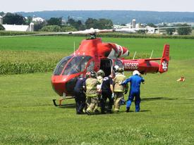 The child is carried to the awaiting helicopter